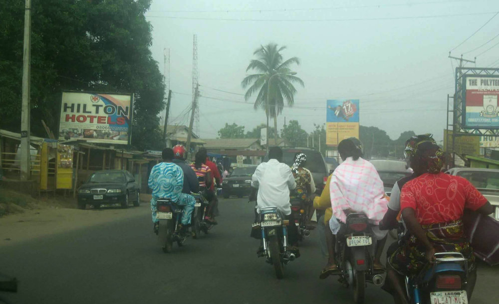 A typical street view from the inside of a car, crossing a town, on the road in Nigeria. © Ilé Àrìrà