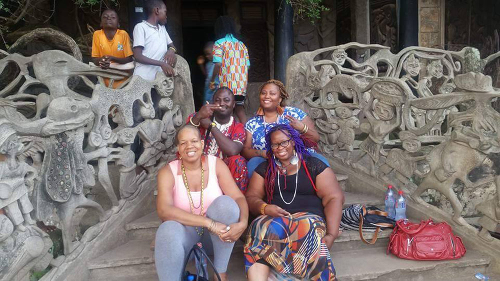A visit to Susanne Wenger's house in Òṣogbo. It can be visited today as a museum, maintained by Adédoyin Fáníyi Ọlọ́ṣun, Wenger's daughter. The house is built in the Afro-Brazilian style, introduced by the Àgùdà, returned Yorùbá-slaves, in 19th century. Sitting in the back Ṣàngówálé Àjàlá and his wife Ọyawùnmí Àjàlá. © Ilé Àrìrà