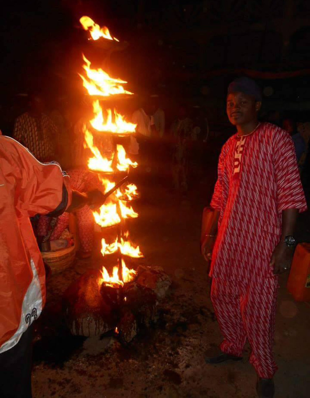 The Ọ̀ṣun festival starts with the lightening of the 16 flames of ọ̀pá osoòrò, an oil lamp commemorating the encounter of Timẹhin with a group of 16 spirits of Òrìsà Ọ̀sanyìn before Òṣogbo was founded. It burns all night long. Here with Ṣàngóṣakin Àjàlá. © Ilé Àrìrà