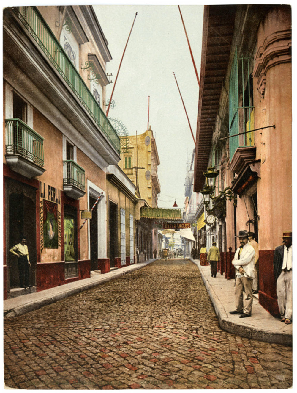 A view every tourist knows: Calle Obispo in La Habana Vieja. The shopping street today for tourists and place to sip a Mojito, before heading back to Varadero with your guáguá, the hand-colored photo is from 1900. Cuban Photograph Collection by the  University of Miami Libraries . Image Public Domain.