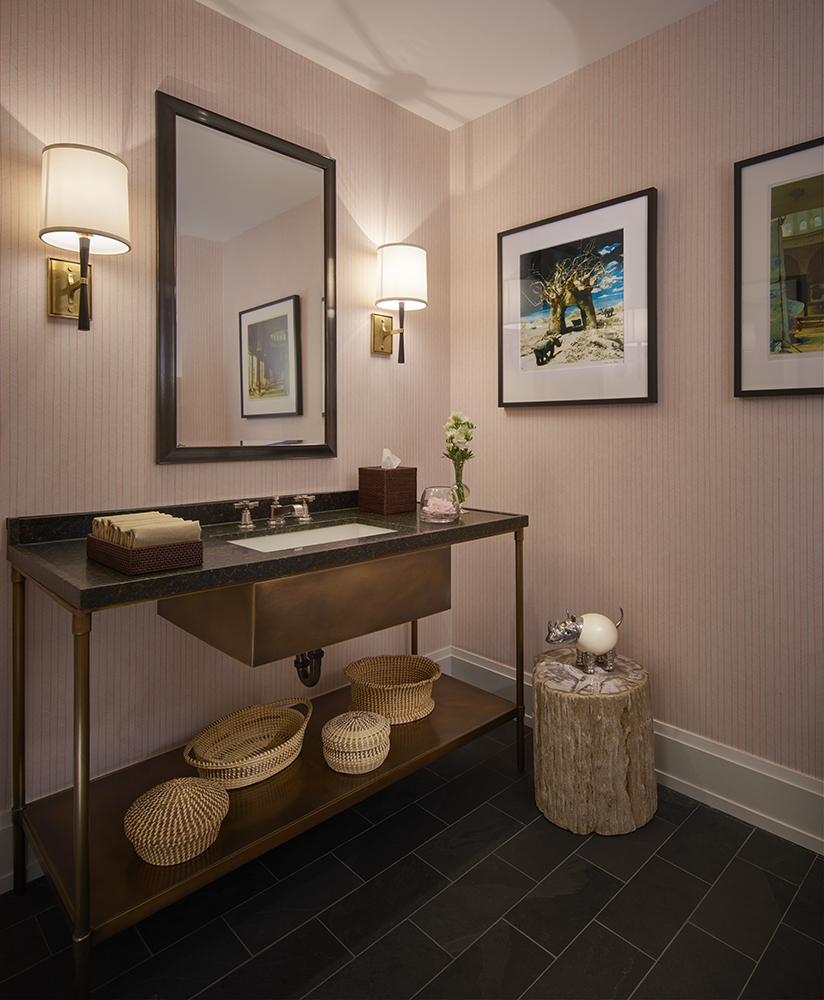 "The Powder Room walls are clad in Hermes ""Herringbone"" wallpaper. A collection of dioramas are displayed with a group of straw grass baskets."