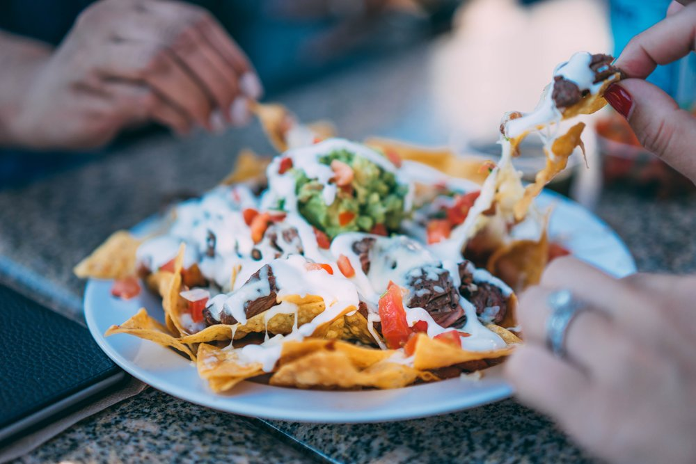Four friends eating nachos