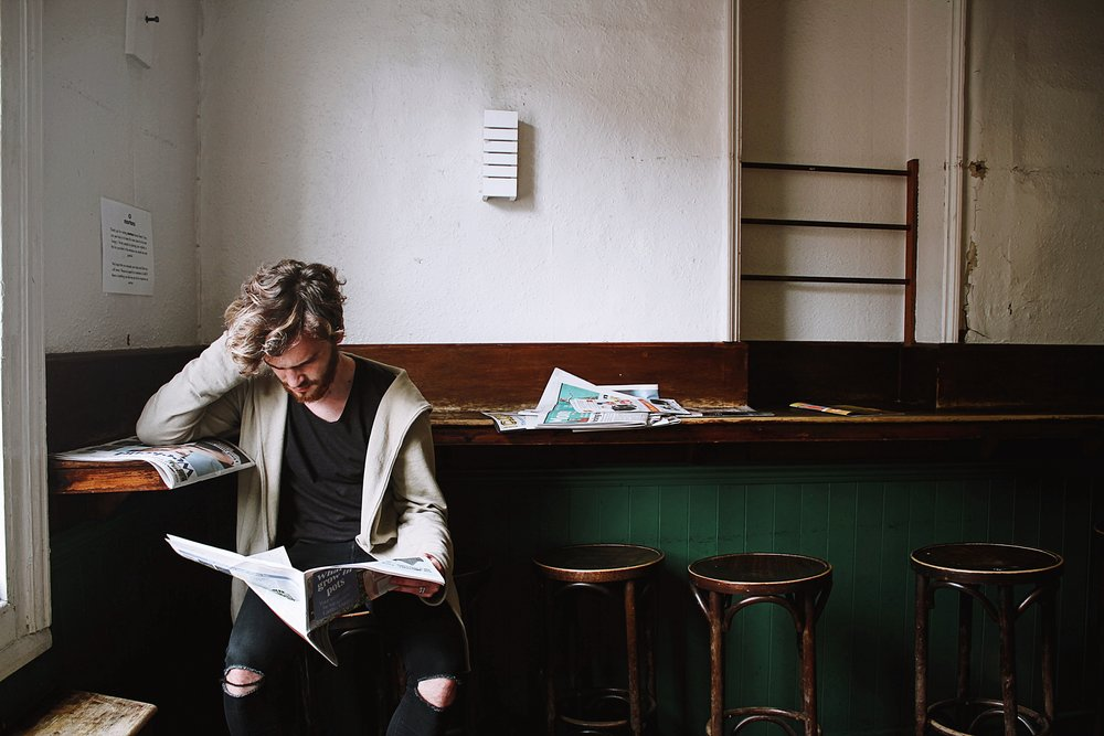 Man sat in a cafe reading a paper