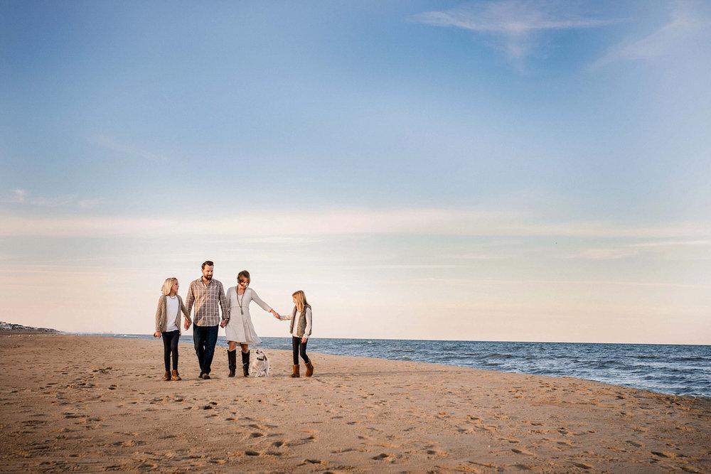 family-dressed-in-neutral-tones-walks-along-sand-sandbridge-beach-virginia-beach-photographers-melissa-bliss-photography.jpg