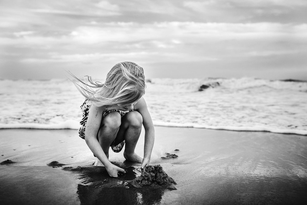 young-girl-digging-in-the-sand-black-and-white-virginia-beach-picture-melissa-bliss-photography.jpg