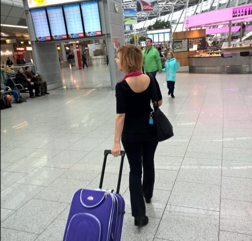 Bildet viser kvinne med koffert på flyplass