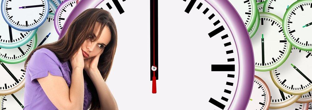 Kvinne som ser betenkt ut omgitt av klokker