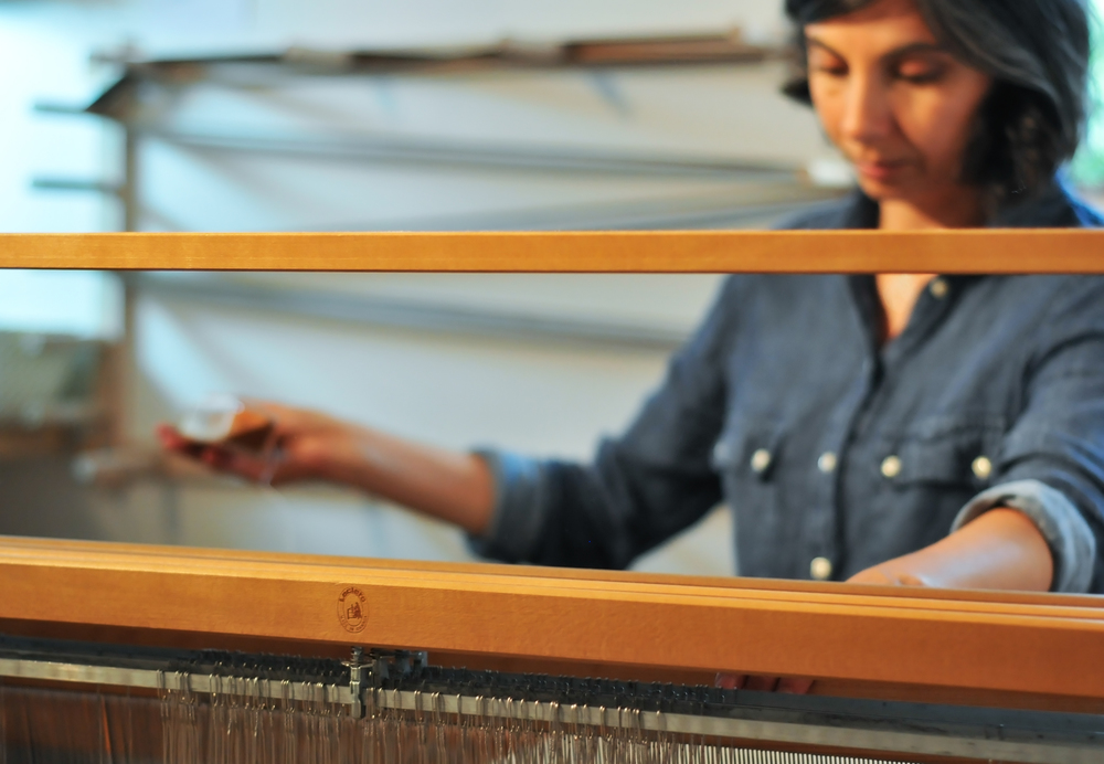 A young student weaving on the Woolhouse table loom in a kindergarten workshop.