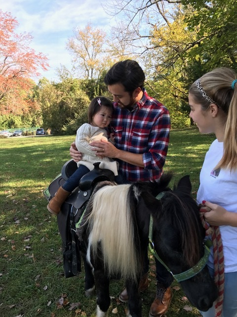 Riv's very first pony ride. Reluctant at first she touched the soft pony's mane and thoroughly enjoyed the short ride.