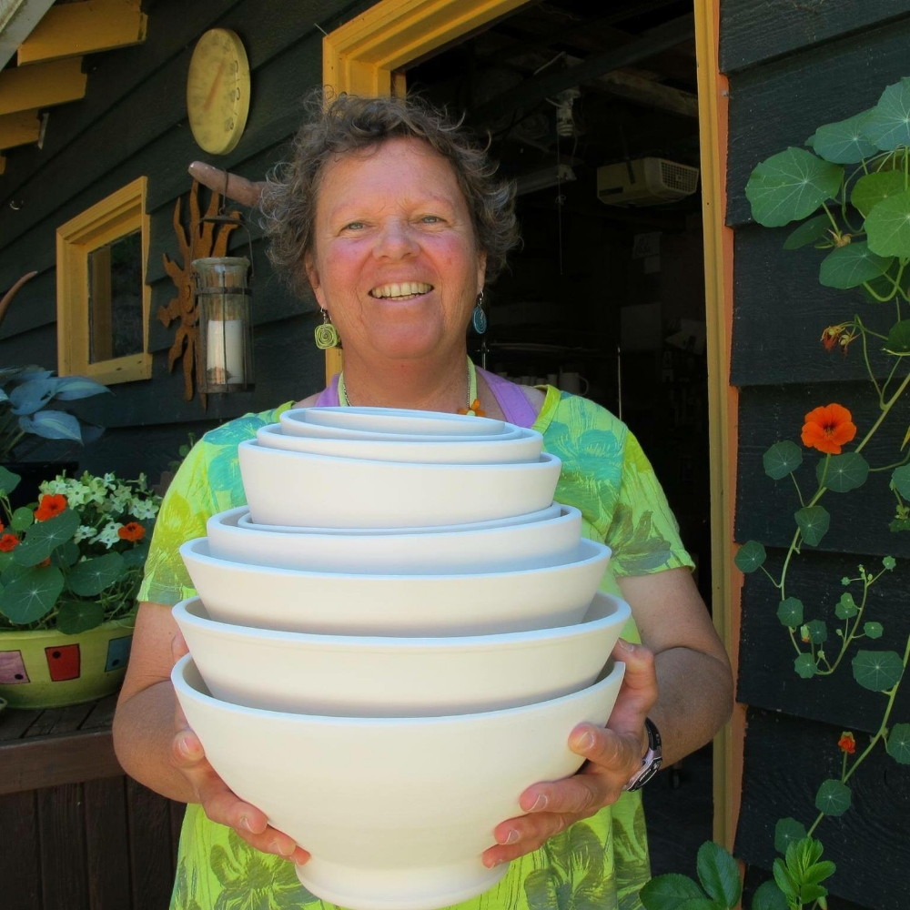 Diana  Cronin with a stack of bowls fresh out of the bisque kiln