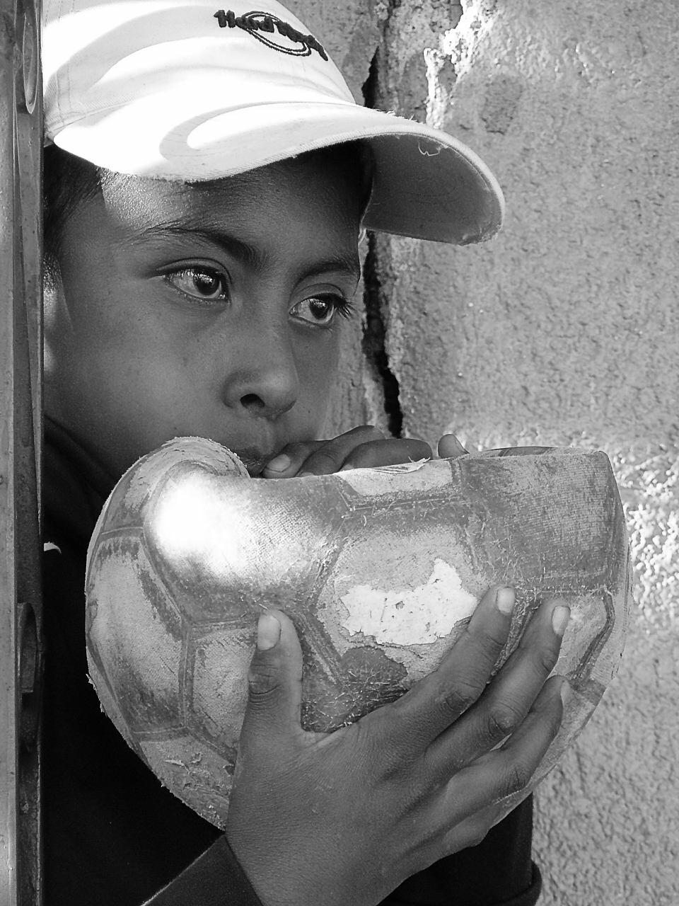Un niño con su balón de Fútbol observa mientras la comunidad vota para decidir si están de acuerdo o no con el proyecto minero en su comunidad.