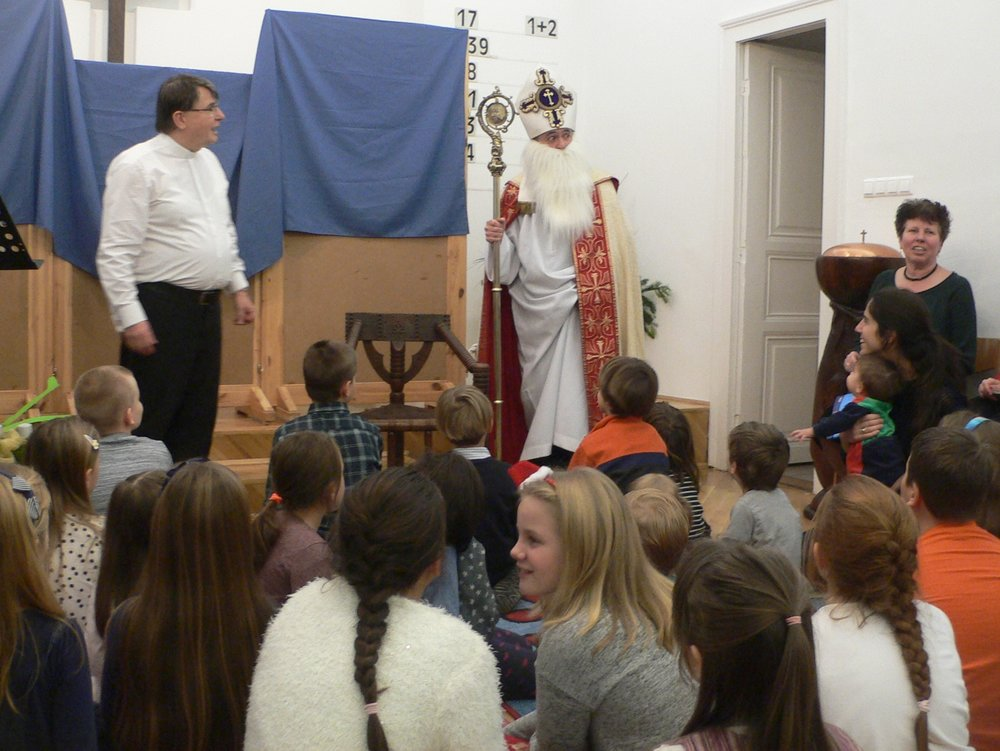 """A gyermekek a MIklós püspök legendájáról írt énekkel köszöntöttök, amelynek refréne így szól: """"Benne élt a szeretet, Jézus így követte! Szeretettel segített, úgy mint a Mestere!"""" Miklós püspök az alkalmat vezető lelkész kérdéseire elmesélte az életét, amelyet a gyermekek érdeklődve figyeltek. S megtanulták a Mikulástól, hogy alázatosan, az emberek baját meglátva és szeelid szeretettel segítve kell járni az élet útján. Majd ők is énekelték: A világon jól ismert Miklós, a szent ember Minden évben rágondolunk nagy szeretettel! Hisz Jézus barátja ő, és hű követője! Aki Jézust szereti, tanuljon hát tőle!"""