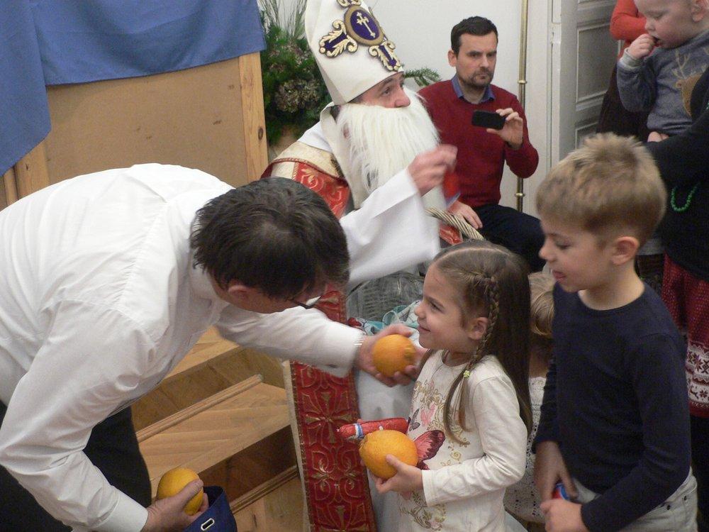 Természetesen a MIkulás is osztott jelképes ajándékot a gyermekenek, majd megáldotta jelenlévőket. A vidám gyermekcsapat még fényképezkedhetett is a Mikulással, akinek azátn másokhoz is sietni kellett. A bábjáték szövege és a Miklós püspökről szóló ének a Budavári Lelkészi Hivatalból elkérhető!