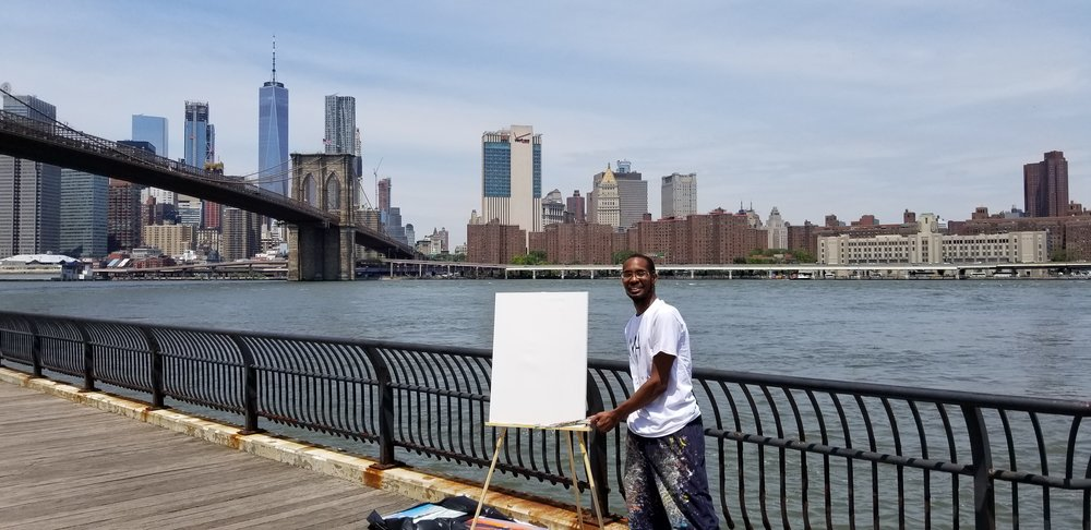 Me displaying my artwork live painting at the Brooklyn Bridge Park over the skyline view of New York city east river.
