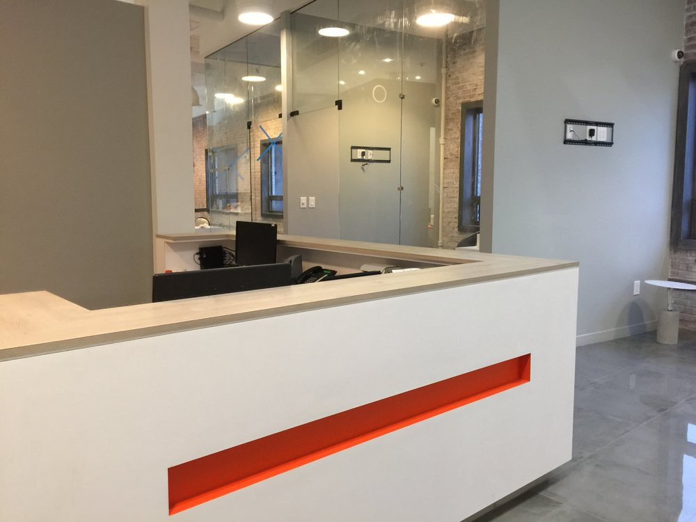 Our front desk! (Behind the desk you can see the glass rooms and the tv mounts ready to display high definition awesomeness!)