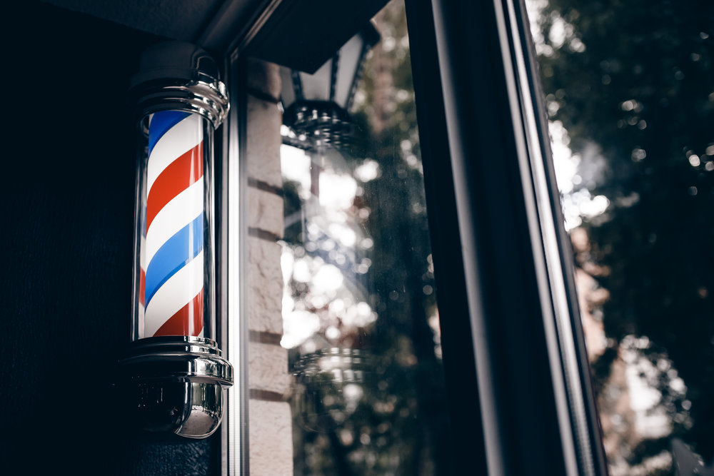 Barber shop pole at entrance of the window. background is dark.