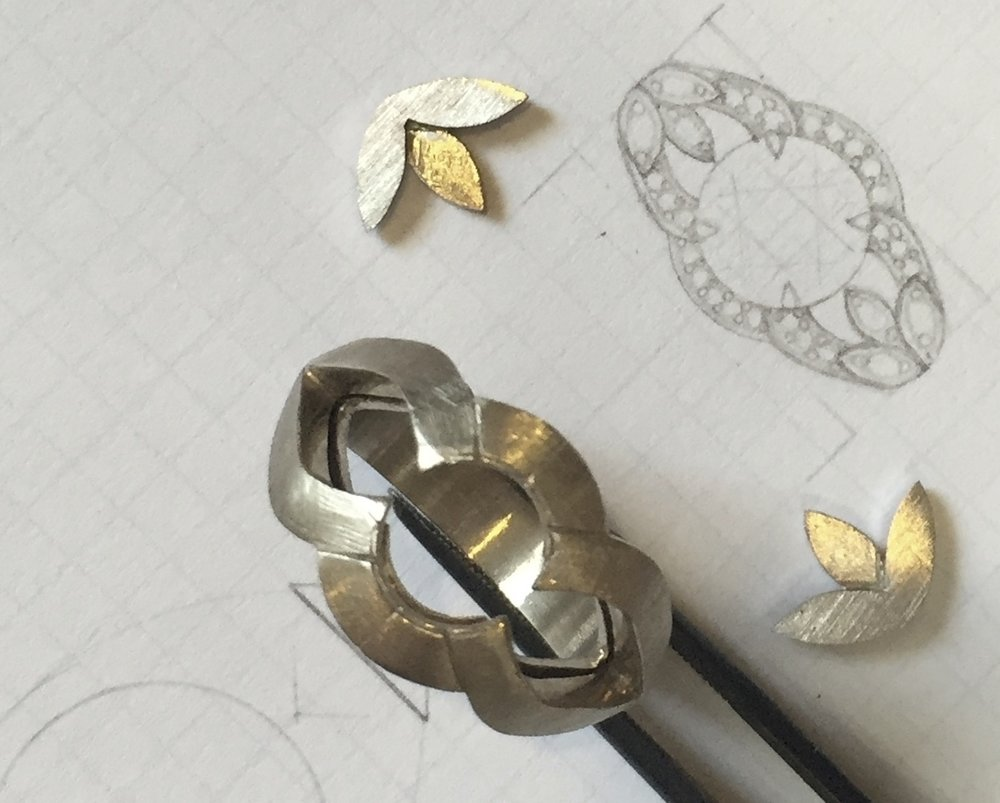 Design Process - This partial halo style engagement ring designed to protect the center diamond has a wide feel and was made to be worn without a wedding band. Hand fabricated with a nod to vintage or period jewelry, this 14 karat white gold and diamond mounting is set in a common bead and bright cut style trimmed in millgrain.