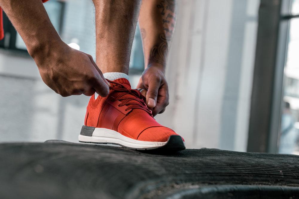 Athlete tying their shoe before a run