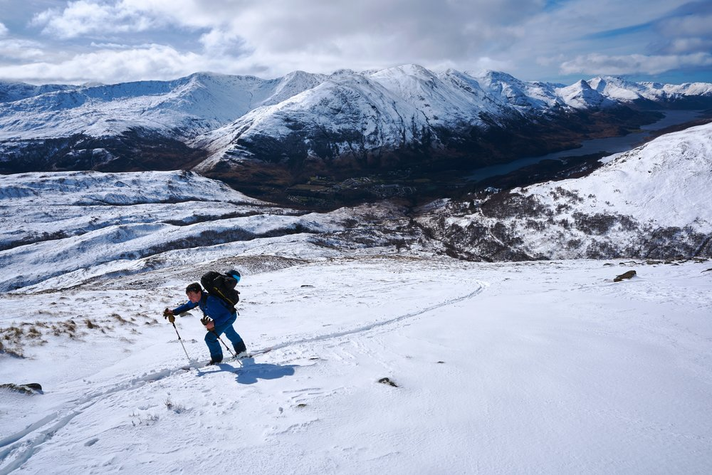 Tom skinning up above an alpine looking Kinlochleven.
