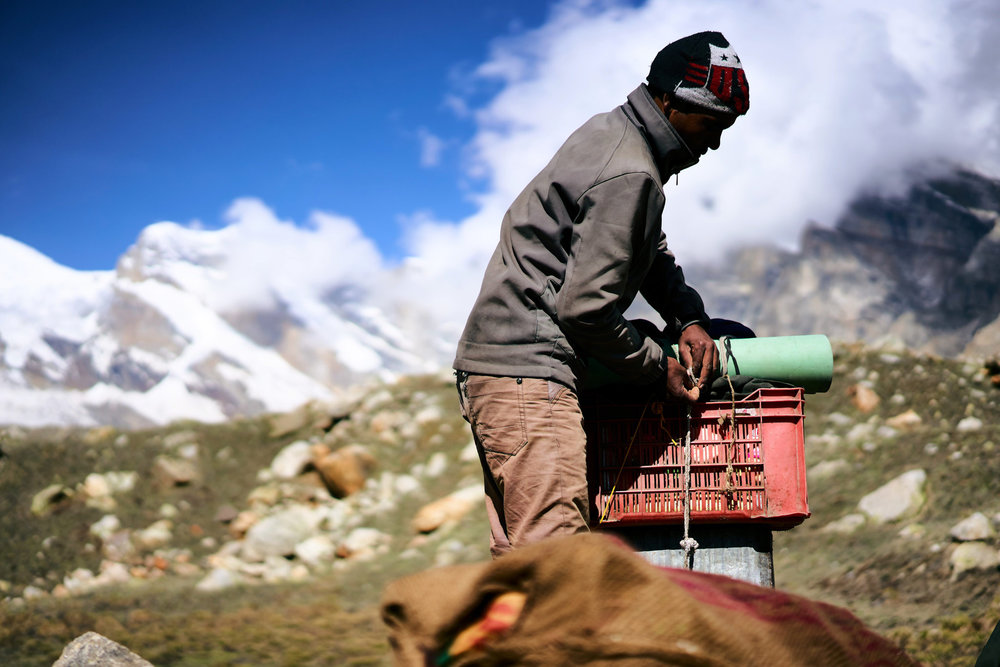 A porter prepares his load, ready to leave basecamp on the way back to Gangotri. Porters are paid by the expedition sirdar in proportion to the weight of the load they carry, so there's usually a lot of  hustling between them when the loads are divied up to secure the heaviest.