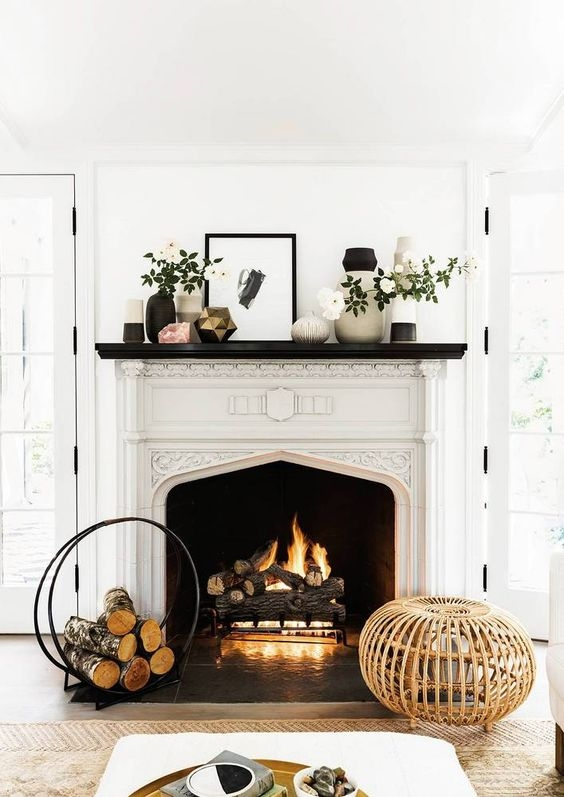fireplace with log holder and black and white vases
