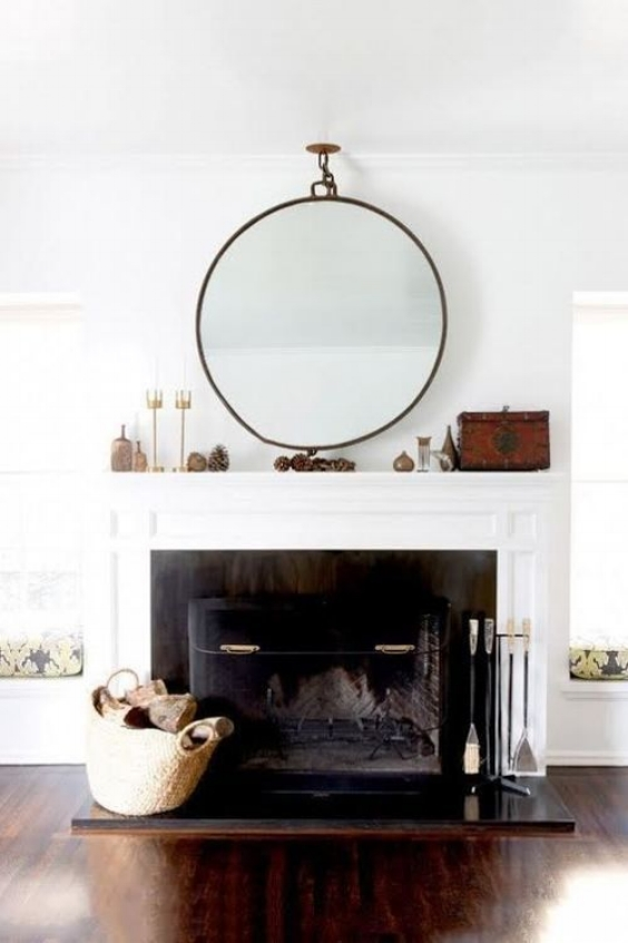 fireplace with large round mirror