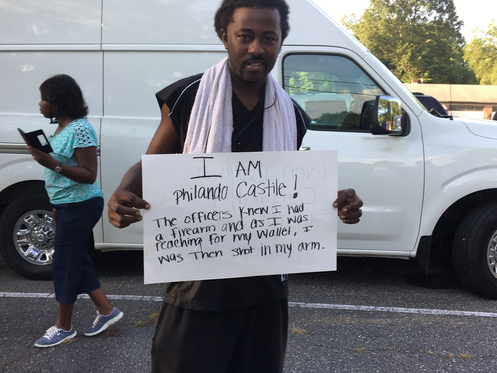 """Anthony Hart carries a sign that reads, """"I AM Philando Castile"""" and describes the reported circumstances of his death in St. Paul, Minn."""