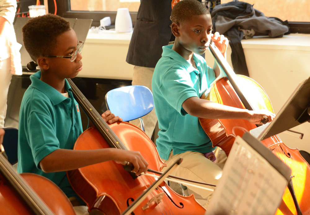 "6th graders in the Abbado string orchestra concentrate play ""Ride of the Valkyries."""