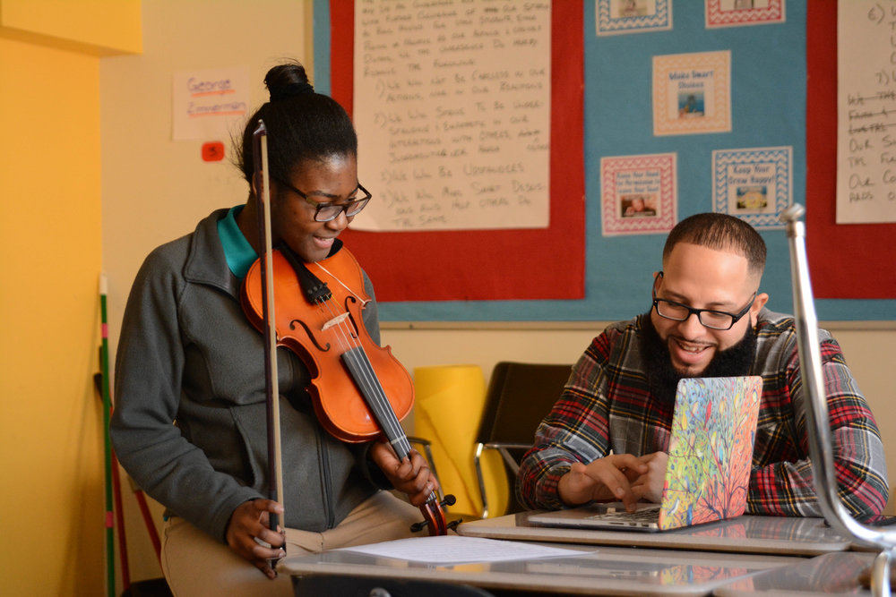 Classroom support assistant Mr. Santiago works with a student to record her playing her original composition.