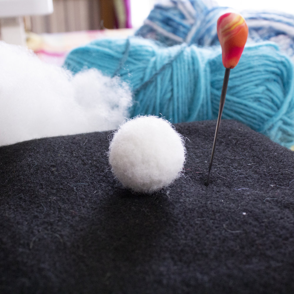 Marble-sized ball needle felted from poly-fil fiber.