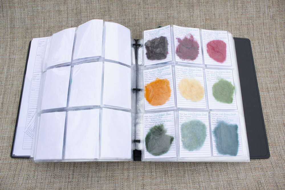 image: open binder with trading card binder sleeves, pockets filled with needle felted flat samples of purchased processed fiber from a vendor. behind them are paper tickets documenting the name and source of the sample