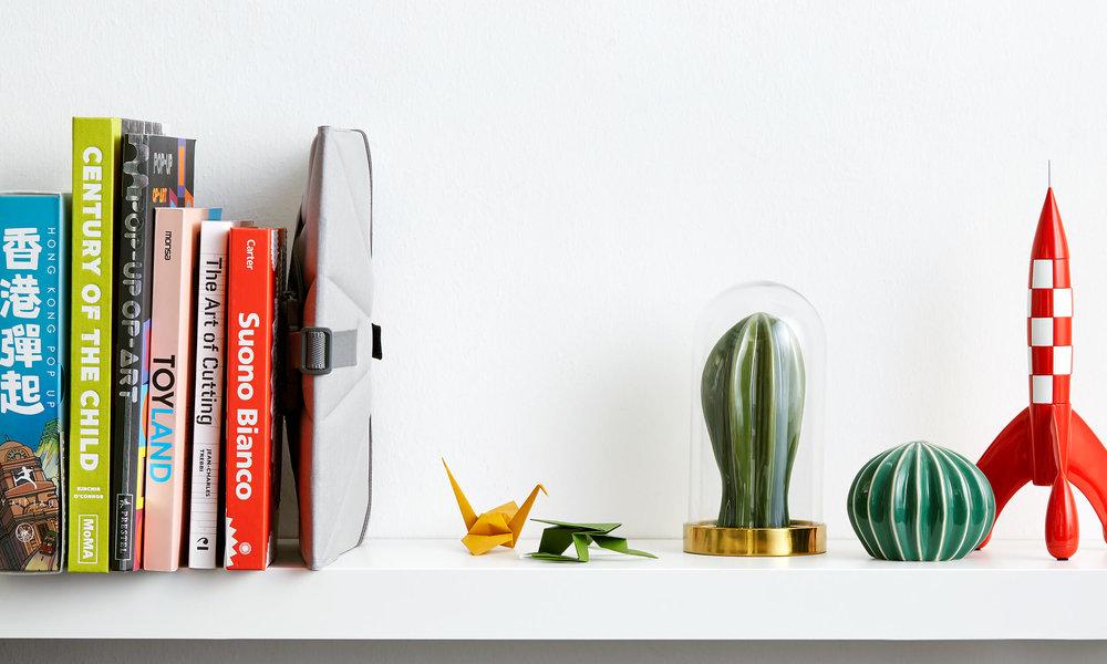 Bombol-Pop-Up-booster-seat-folded-on-book-shelf.jpg