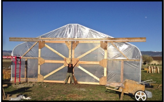 Small farmer, big dreams. Mary stands at the entrance to the newly built--and very large--sliding hoophouse doors.