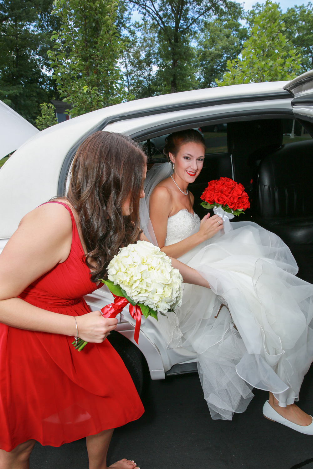 Sister of the bride helping her into the limo