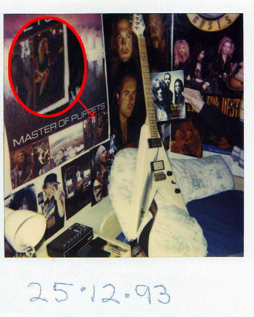 """Here's a pic of my new guitar on Xmas morning 1993; my friend Neil got a Polaroid camera (photo taken with) – that's him also holding up a Nirvana book he got. You can even see James Hetfield holding a similar guitar on the bottom right of the """"Master of Puppets"""" poster on my wall. Nice…"""