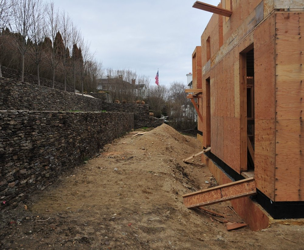 Before the house framing went up, tiered walls were built into the hillside creating planting beds that would be viewed from the second and third floors of the house.  A row of Linden trees were planted in the upper tier of the walls (upper left corner of photo).