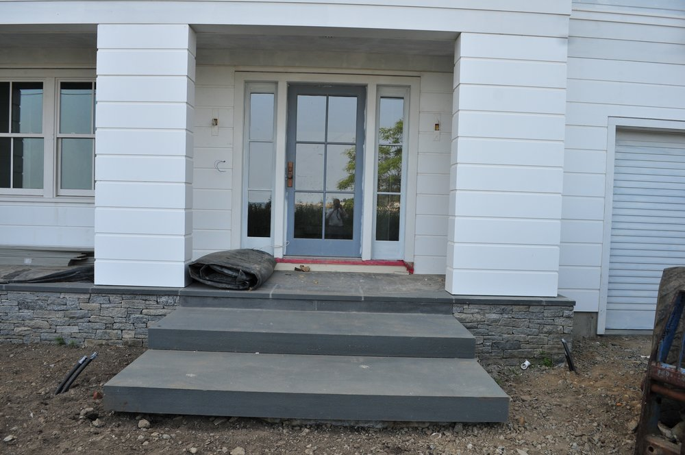 Monolithic bluestone steps are installed to the front entrance