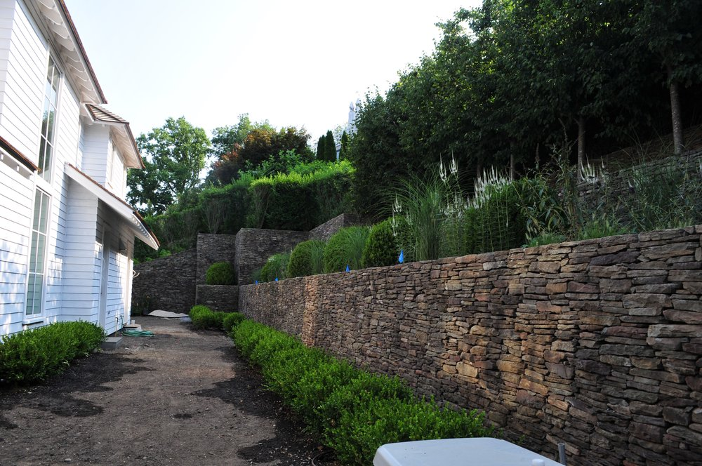 Plantings of boxwood spheres, grasses, and mixed perennials are added to the tiered beds, as well as low boxwood hedging to soften the stone walls and foundation of the house.