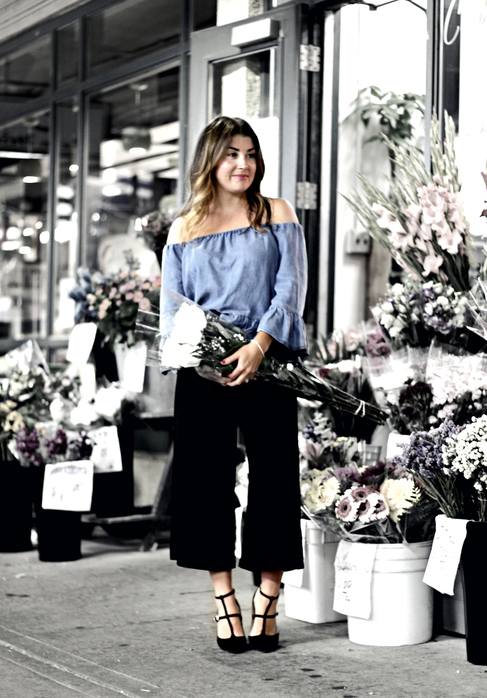 "outside a flower shop at Atwater Market. With her flowy, off-the-shoulder top and wide-legged culottes, Stephanie looked like one of the flowers herself. The shop assistants glanced momentarily at us, like ""what are they doing?"" and then waved obligingly."