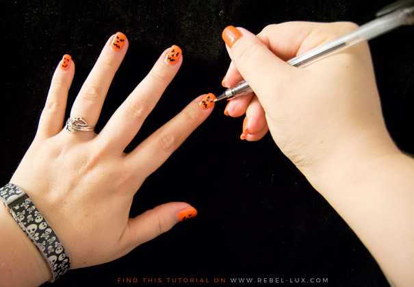 Halloween art being drawn onto fingernails.