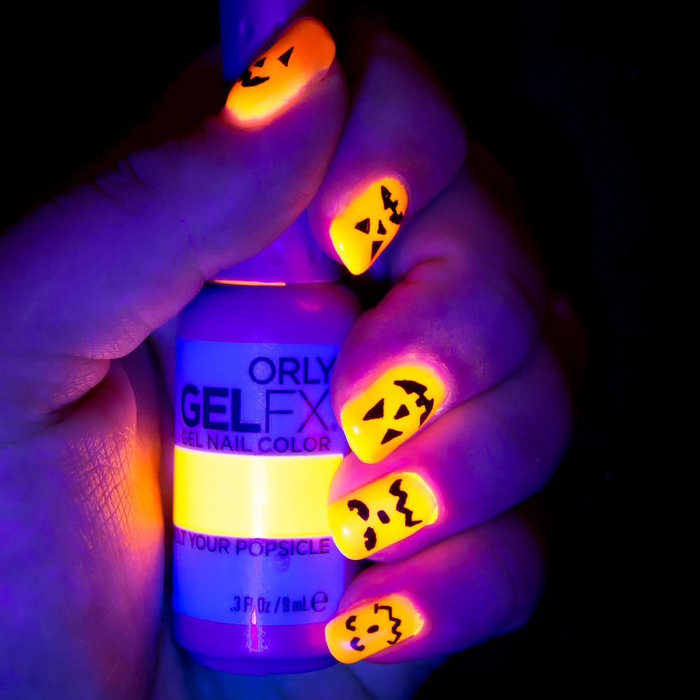 Halloween jack o' lantern fingernail art that glows bright orange under UV light.
