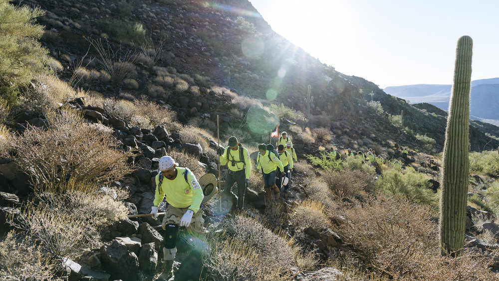 IMAGE CAPTION:  Members of Aguilas Del Desierto crest a hill in the Cabeza Prieta National Wildlife Refuge outside of Ajo, Arizona. For migrants crossing into the United States through this Sonoran Desert route the journey often takes 7-10 days with a guide and costs 2-5 thousand USD.