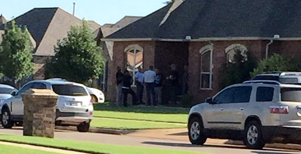 Federal law enforcement officers serve a search warrant of the Gum residence.