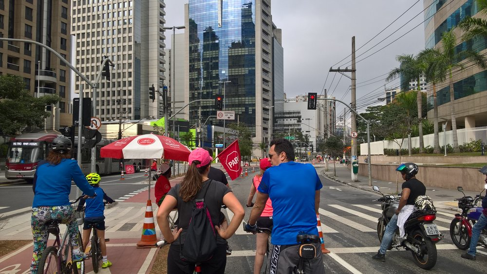 Each bicycle street intersection on Sunday has attendees stopping bikers when the light is red.