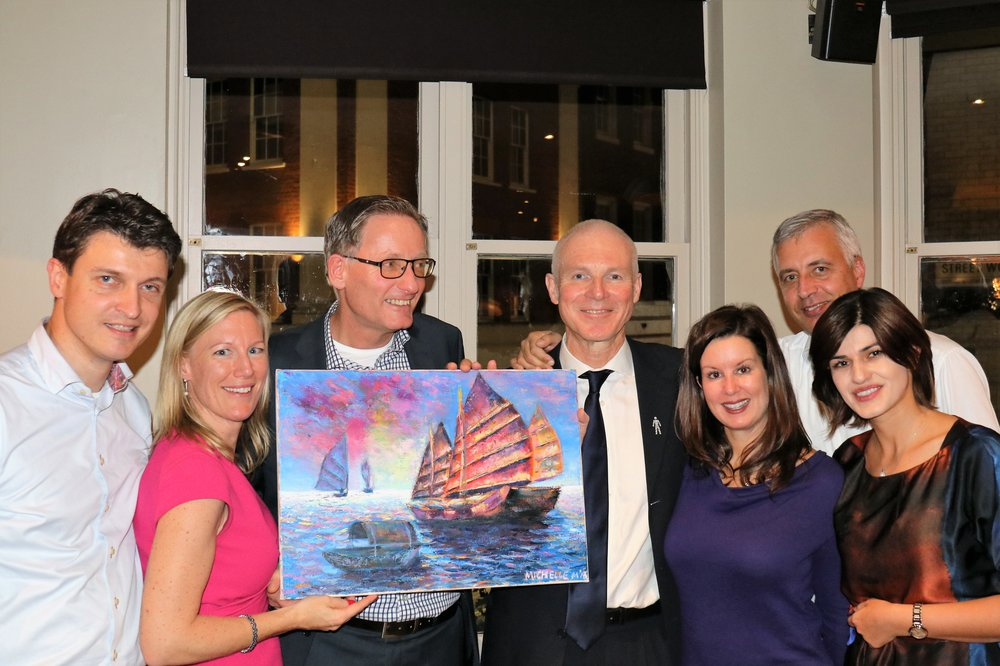 Mick Farrell (wearing the black tie) was delighted when presented by the management team with the painting for his farewell party on 17th November 2016 in London.