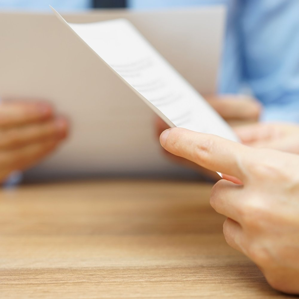 stock-photo-business-partners-reading-and-negotiating-about-legal-document-380378131.jpg