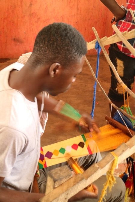 community member weaving kente cloth