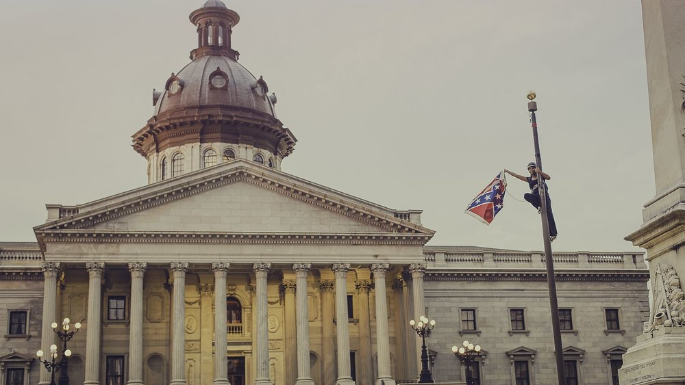 Bree Newsome removes the confederate flag outside the South Carolina Statehouse, 2015;  photo: Adam Anderson