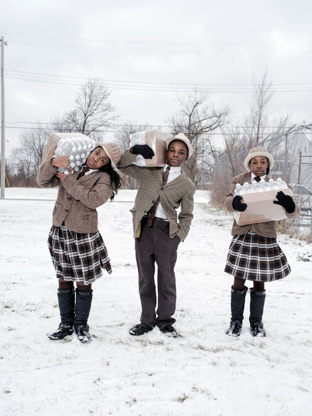 In Flint, Michigan, siblings Julie, Antonio, and India Abram collect their daily allowance of bottled water from Fire Station #3, their local water resource site; photo: Wayne Lawrence
