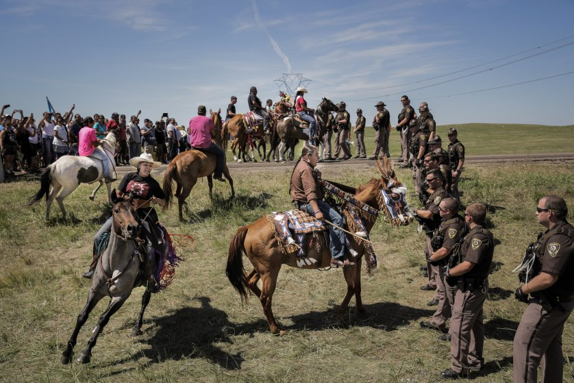 Lakota riders Alex Romero-Frederick (left) and Greg Grey Cloud (right) confront a line of North Dakota State Police the day that construction crews began work on the Dakota Access Pipeline just outside the Standing Rock Reservation, on August 15, 2016. The display was part of a ceremonial horse introduction meant to be peaceful.     photo: Daniella Zalcman